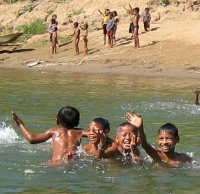 Boys swimming in tributary of Mekong River.